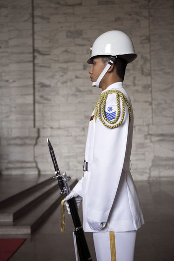 Clothing Hat Headwear Helmet Holding Indoors  Occupation One Person Protection Real People Rear View Safety Security Standing Three Quarter Length Traditional Clothing Uniform Wall - Building Feature White Color Women