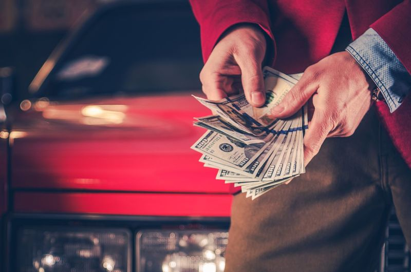Midsection of man holding currencies while leaning on car at night