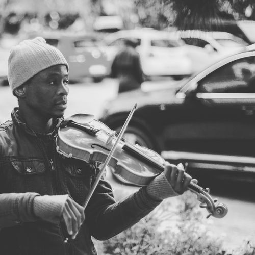 Man playing violin on street in city