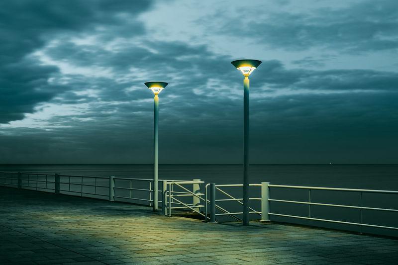 Street light by sea against sky at dusk