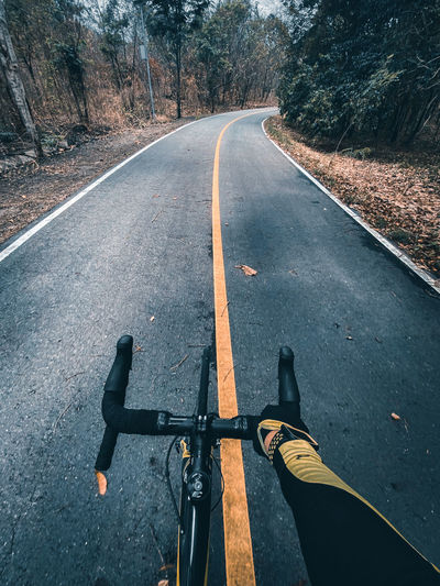 Personal perspective of man riding bicycle on road