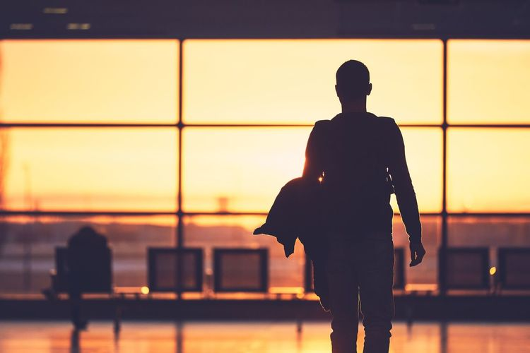 Silhouette man walking at airport during sunset