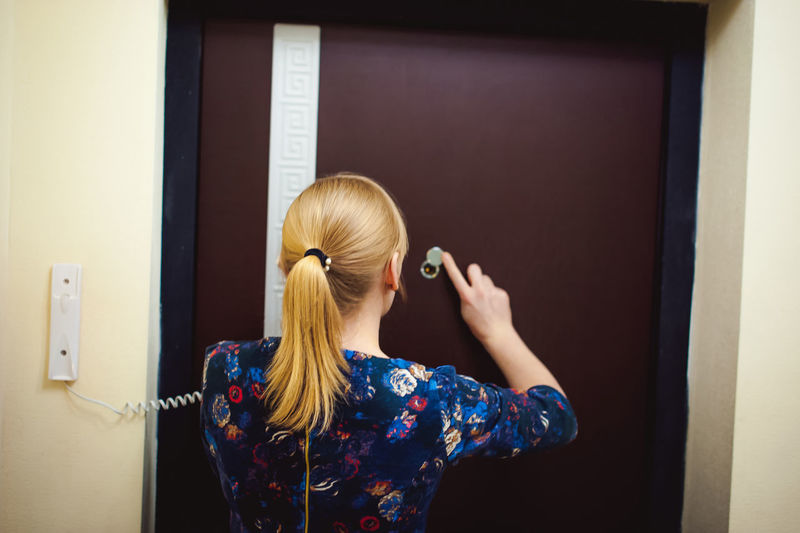 Rear view of woman talking on telephone while standing against door