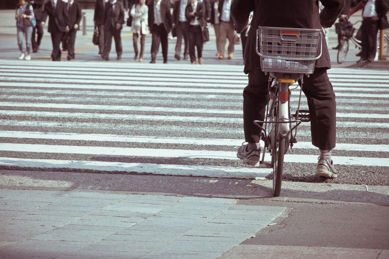 Low section of man cycling while business people walking on road