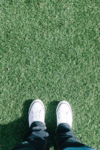 Standing on artificial sports field grass with two feet Adult Close-up Copy Space Day Grass Green Color High Angle View Human Body Part Human Leg Low Section One Person Outdoors People Personal Perspective Shoe Sports Standing Texture