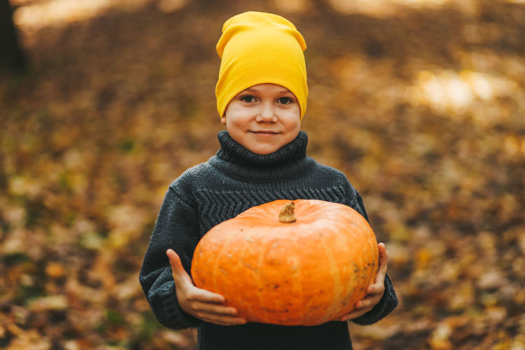 Happy funny little boy teen child in a hat holding a big pumpkin is getting ready for halloween