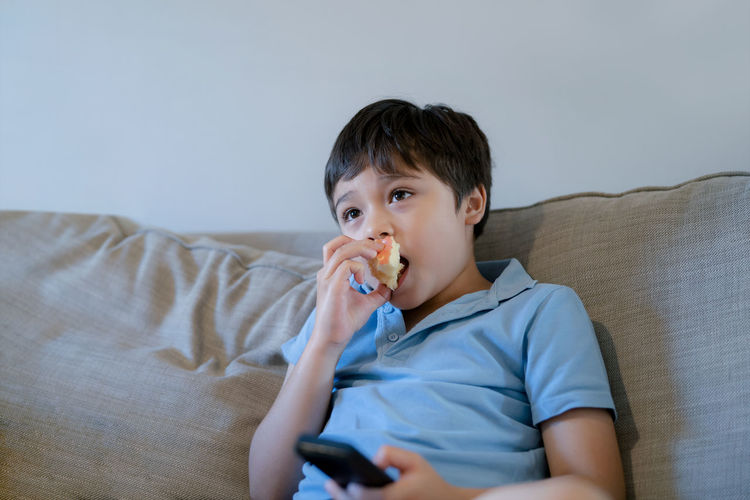 Portrait of boy looking away while sitting on sofa at home