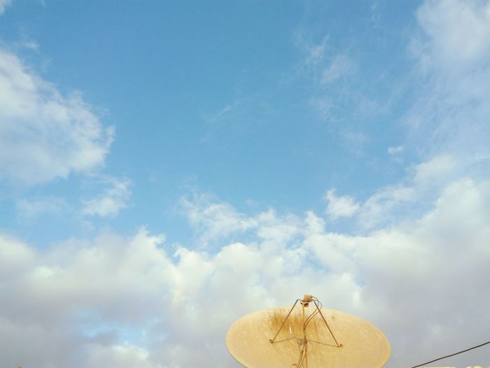 Low angle view of antenna against cloudy sky