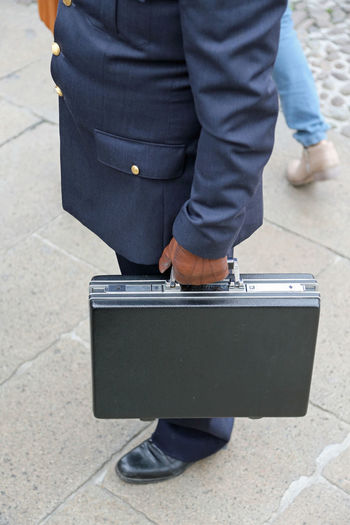 Low section of businessman with suitcase standing on footpath
