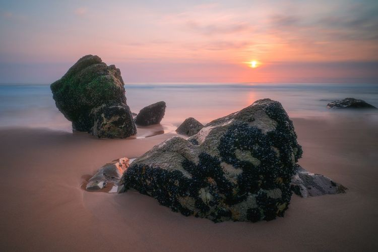 Rocks on shore against sky during sunset