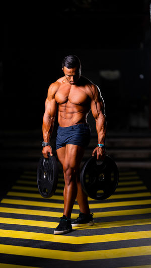 Full length of shirtless man holding weights while walking on floor