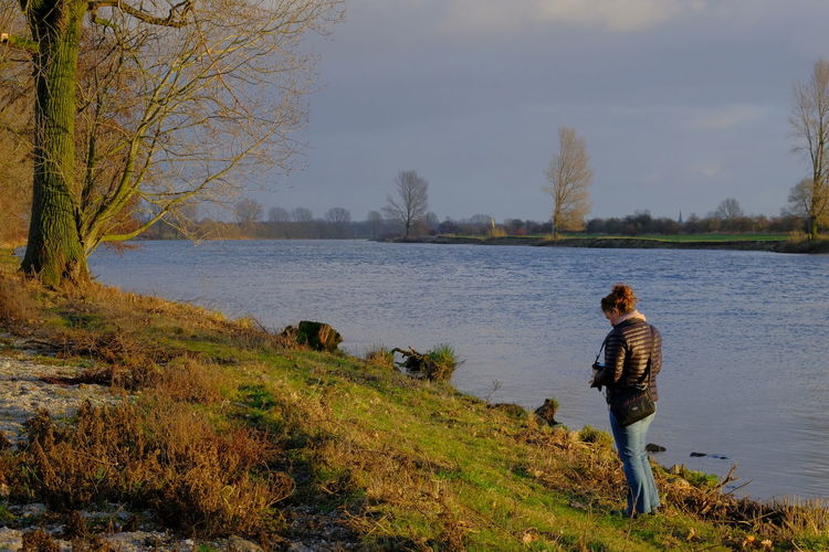 Rear view of woman holding camera while standing on grass by lake against sky