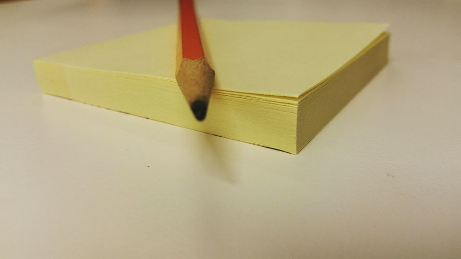 Close-Up Of Adhesive Notes And Pencil On Table
