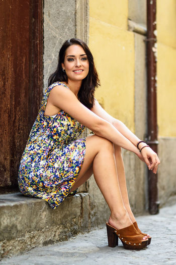 Girl with blue eyes smiling sitting on urban step. Young woman wearing flower dress in urban background. Beauty and fashion concept. Adult Beautiful Woman Beauty Day Fashion Full Length Hair Hairstyle Happiness Leisure Activity Lifestyles Looking At Camera One Person Outdoors Portrait Real People Sitting Smiling Women Young Adult Young Women