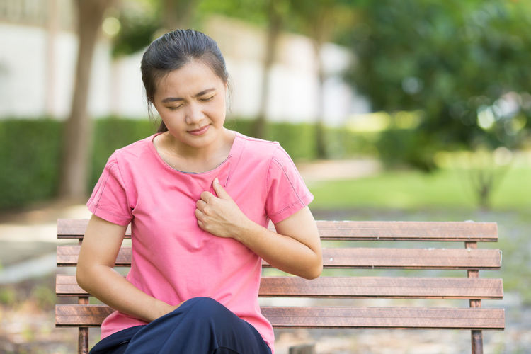 Young woman suffering from chest pain while sitting on bench at park
