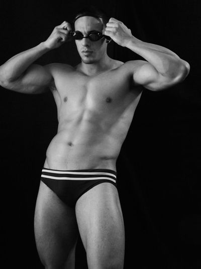 Muscular man wearing swimming goggles over black background