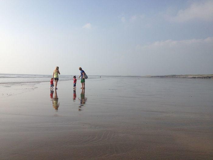 Family at beach against sky