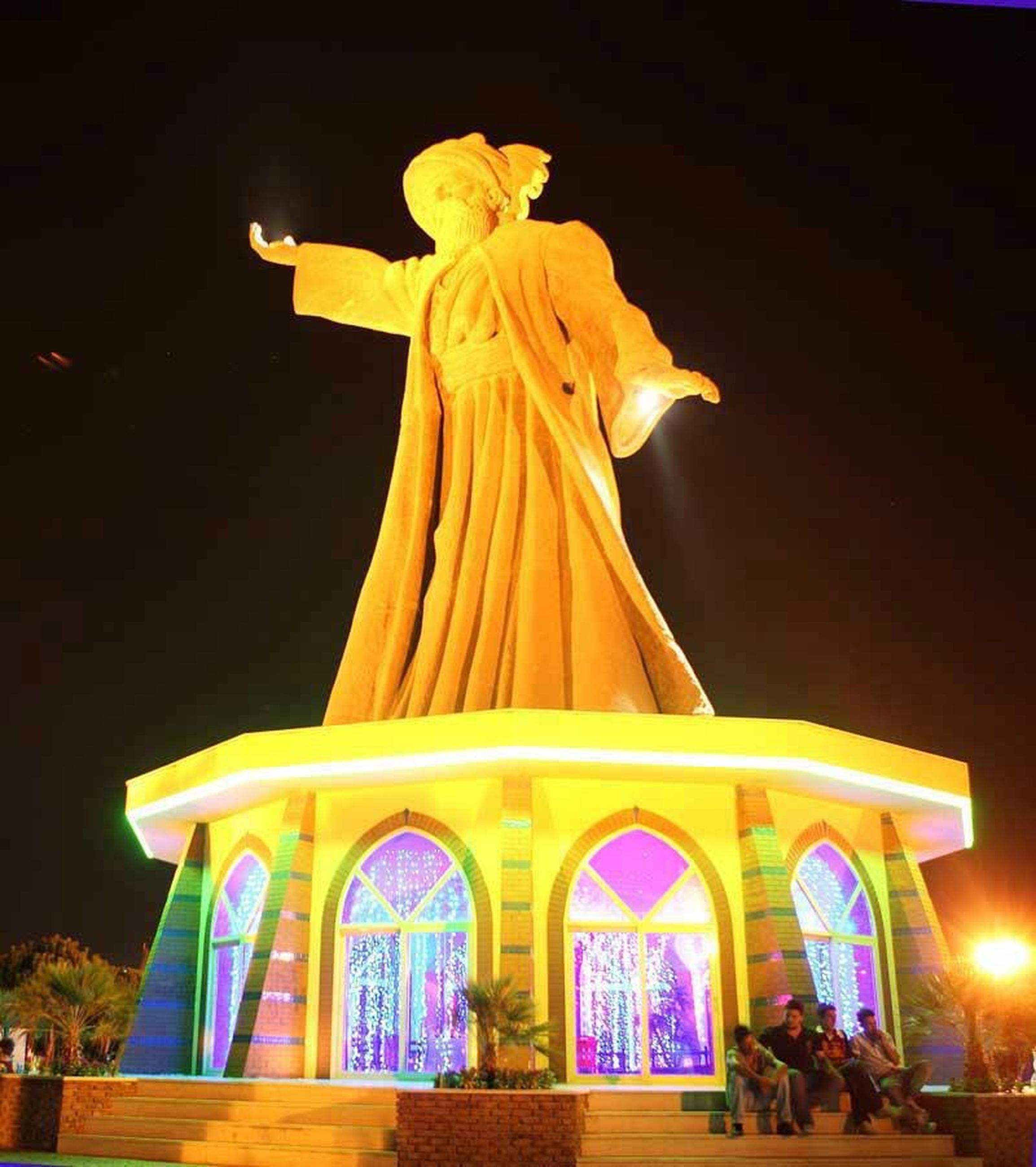 night, human representation, art and craft, statue, art, sculpture, illuminated, creativity, religion, low angle view, spirituality, animal representation, place of worship, built structure, carving - craft product, no people, clear sky