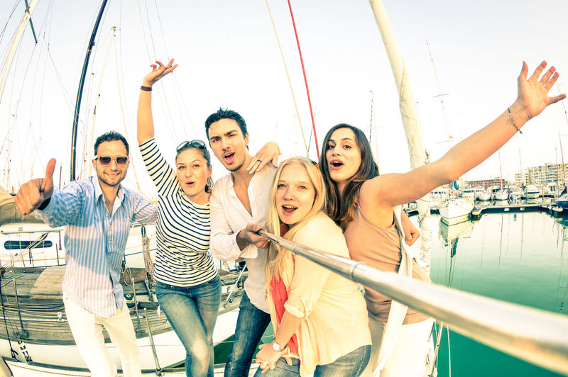 Group of friends having fun on sailboat adventure trip - Wanderlust travel concept with young people on sail boat world tour Travel Rich Lifestyle Sail Boat Sailing Sailboat Sailingboat Luxury Yacht Selfie Stick Party Friends People Trip Young Moment Cruise Group Pic Beach Summer Happy Millennials
