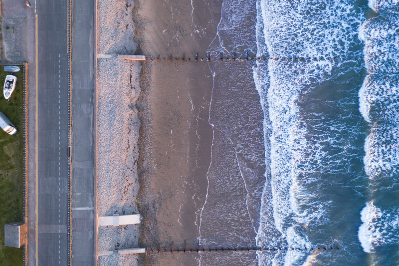 Directly above shot of waves in sea by road