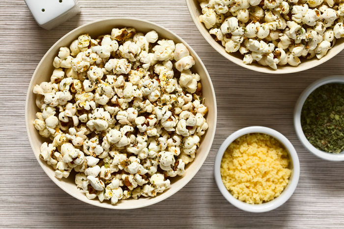 Homemade fresh savory popcorn with cheese, garlic and dried oregano in bowls, photographed overhead with natural light (Selective Focus, Focus on the top of the popcorn) Crispy Garlic Herb Homemade Homemade Food Bowl Cheese Cheesy Corn Crisp Food Food And Drink Fresh Freshness Oregano Overhead View Pop Corn Popcorn Popped Puffed Salty Savory Savory Food Seasoned Snack