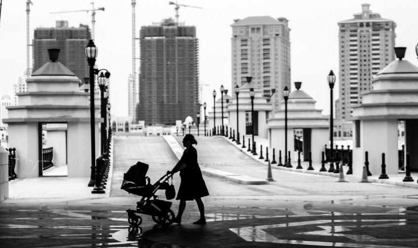 Side View Of Mother With Baby Carriage Walking Against Buildings In City