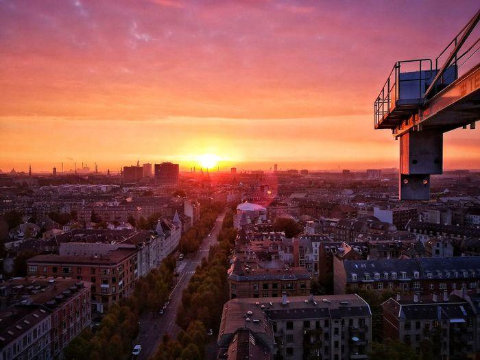 Cherry picker over cityscape against sky during sunset