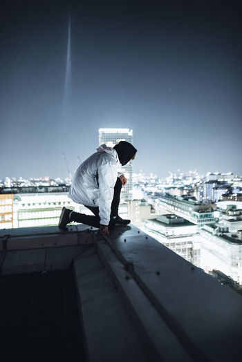 Rear view of man working against sky in city