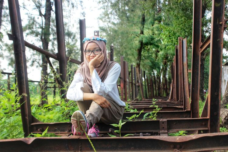 Portrait of young woman sitting on rusty metal against trees