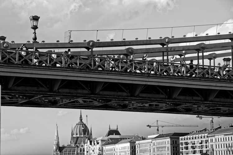 People on bridge against sky in city