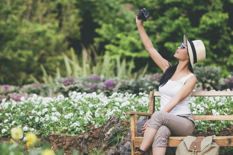 Woman Taking Selfie Through Camera At Botanical Garden