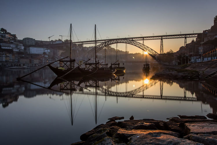 Reflection of bridge by boats moored on river at sunset
