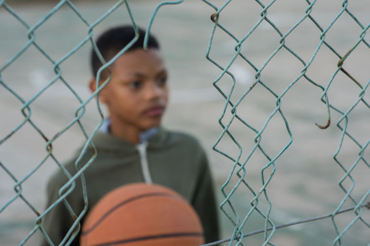 through the wire Barrier Basketball - Ball Basketball - Sport Boundary Boys Chainlink Fence Child Childhood Day Fence Headshot Leisure Activity Lifestyles One Person Portrait Pre-adolescent Child Real People Sport