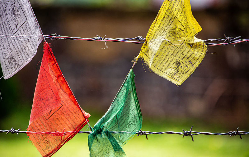 Close-up of prayer flags on fence