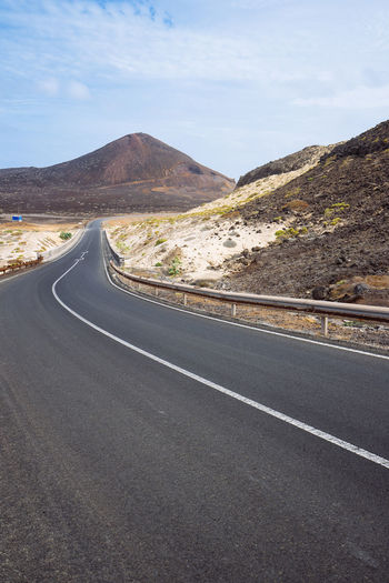 Desolates straight road over a surreal landscape with majestic volcano creater in the distance. Sao Vicente Cape Verde. Cape Verde Cloud - Sky Crash Barrier Day Direction Dividing Line Empty Road Landscape Marking Mountain Mountain Range Nature No People Non-urban Scene Outdoors Road Road Marking Scenics - Nature Sign Sky The Way Forward Tranquil Scene Tranquility Vulcanic Landscape Winding Road