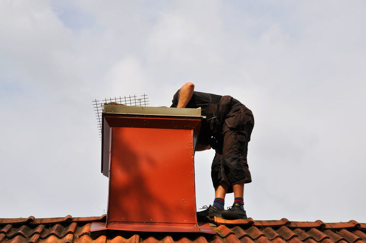 Chimney sweep checking out chimney on the roof of a house. Architecture Built Structure Checking Out Chimney ChimneySweep Cloud - Sky Day Inspection Low Angle View Man Outdoors Proffesion Roof Standing