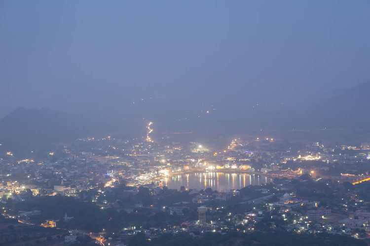 misty scene of Pushkar town and Pushkar lake from Savitri Temple hill in twilight time, Rajasthan, India Aerial View Blue City Cityscape Illuminated India Indiapictures Landscape Light Mountain Nature Night Night View Outdoors Pushkar Scenics Travel Destinations