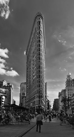 People on street by flatiron building against sky