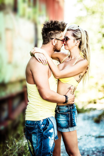 Two People Togetherness Three Quarter Length Love Real People Bonding Positive Emotion Young Adult Emotion Couple - Relationship Young Women Women Men Standing Lifestyles Focus On Foreground Young Men Adult Shirtless Casual Clothing Shorts Outdoors Hairstyle
