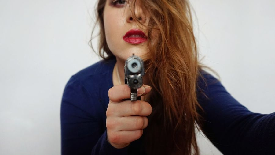 Close-Up Portrait Of Young Woman Holding Handgun Against White Background