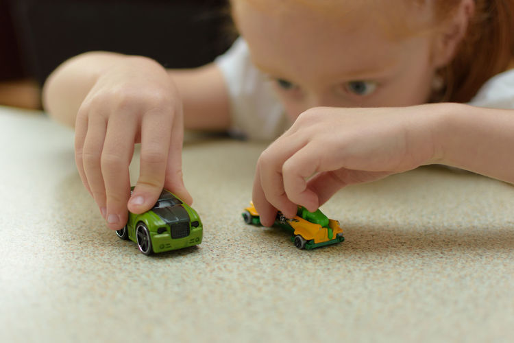 Close-up of girl playing with toy cars on table