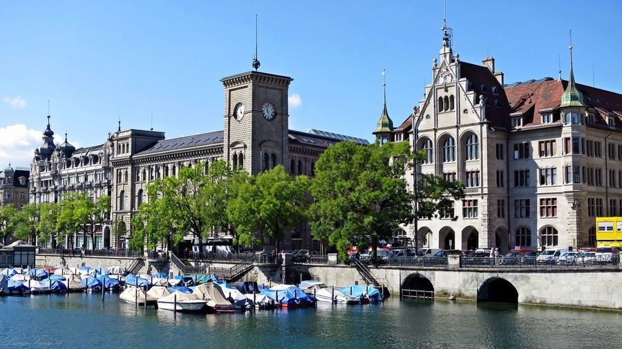 Boats moored on limmat river by buildings in city against sky