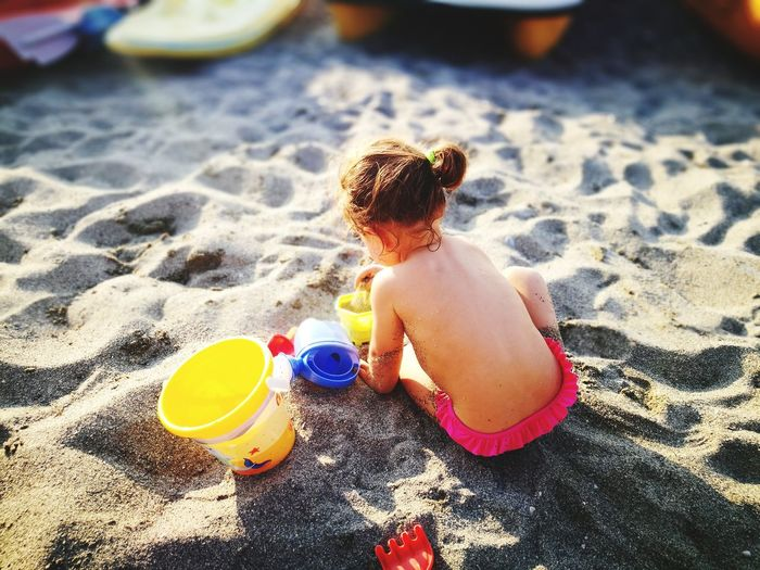 Rear view of shirtless baby girl playing with sand at beach