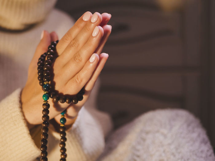 Cropped hands with rosary beads
