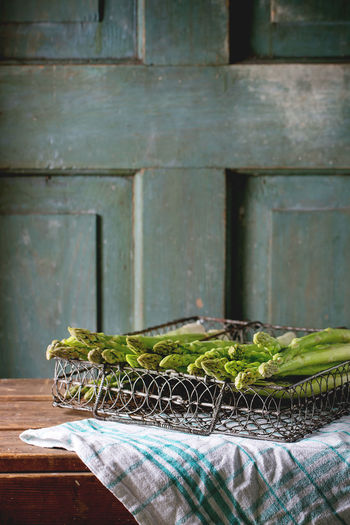 Green asparagus in vintage metal grid box over wooden table with turquoise wooden background. Dark rustic atmosphere Agriculture Asparagus Box Cooking Dark Photography Food Fresh Green Asparagus Harvest Healthy Eating Ingredient Organic Food Raw Food Rustic Salad Seasonal Table Uncooked Vegetables Vintage Wooden