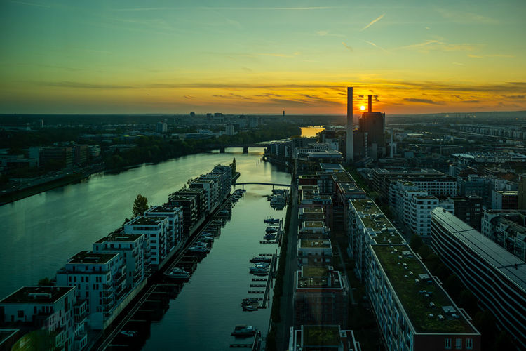 High angle view of river in city against sky during sunset