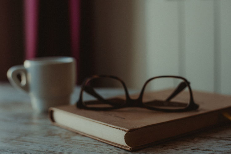 Film Grain Grain Eyeglasses  Personal Accessory Wood - Material Selective Focus Surface Level Focus On Foreground Food And Drink Refreshment Book Drink Coffee Cup Coffee Glasses No People Coffee - Drink Publication Table Cup Mug Still Life Indoors  Eyeglasses  Close-up