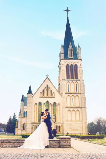Newly Wed Couple Embracing By Church Against Sky