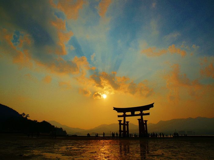 Silhouette torii gate at itsukushima shrine by lake against sky during sunset