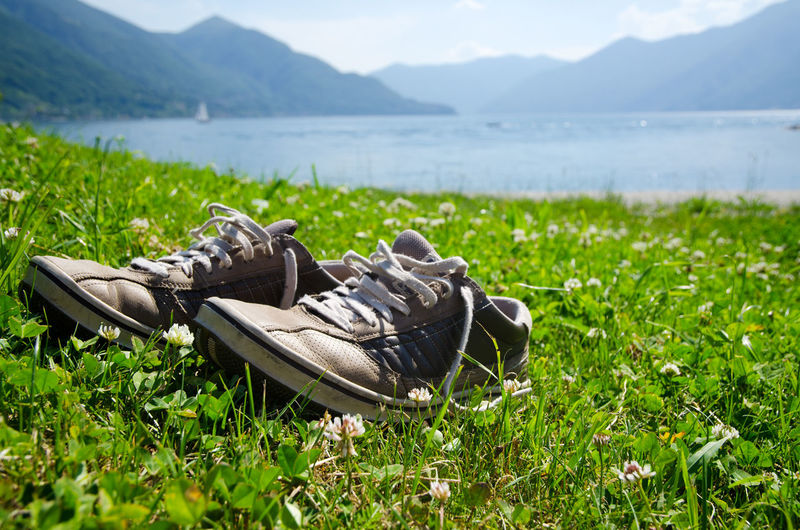 Pair Of Shoes On Grass By River And Mountains Against Sky